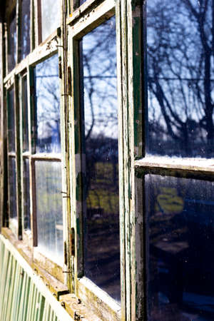 Dilapidated rotten windows on derelict building awaiting demolition with shallow depth of field