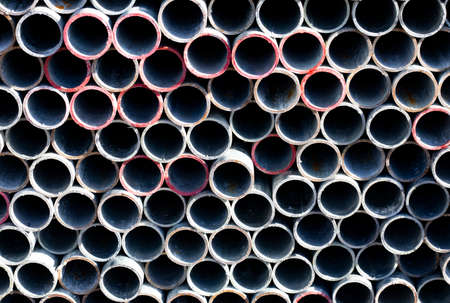 End view on scaffold poles stockpile stacked on storage rack on building construction site