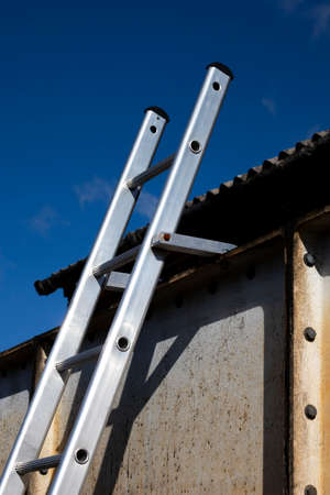 Aluminium ladder securely fastened at top to steelwork to comply with UK health and safety regulations