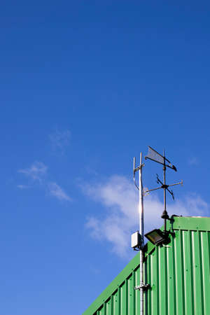 Metal weather vane fixed to top of building to show wind direction with letters indicating the points of the compass Stock Photo
