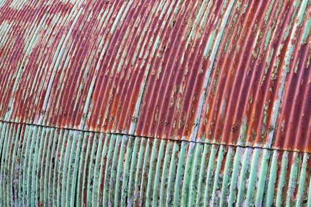 Corrugated steel wall to dilapidated Nissen hut building with flaking green paintwork
