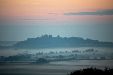 Early morning mist over farmland and woodland in rural Hampshire