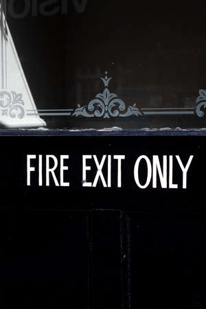 emergency fire exit only sign on black painted timber door to retail premises