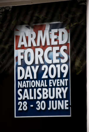 Armed Forces Day national event poster in shop window, held at Hudsons Field and City Centre hosted by Wiltshire Council Editorial