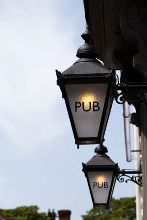 Pub sign on retro style lamp outside public house on period building Foto de archivo