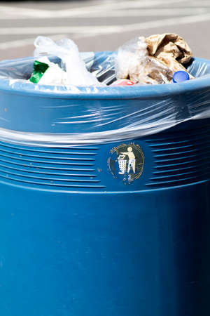 Overflowing blue metal public waste bin with plastic liner Stok Fotoğraf