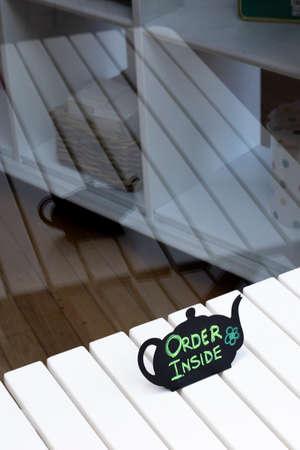Cafe information order inside teapot sign on wooden white table outside premises