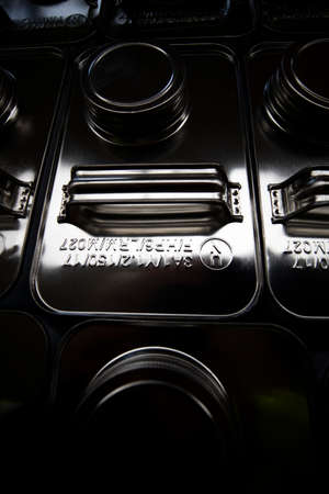 stainless steel jerry cans stacked in warehouse, close up with shallow depth of field