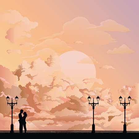 Silhouetted young lovers on a promenade set against a stunning dawn or dusk sky Banco de Imagens