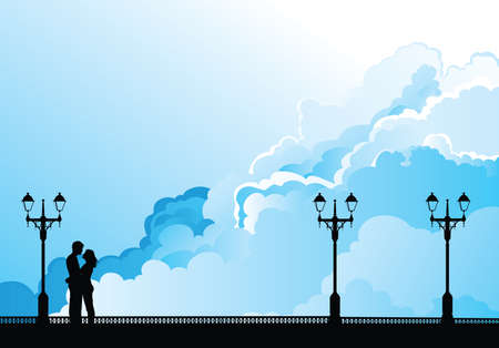 Silhouetted young lovers on a promenade set against a blue cloudy sky