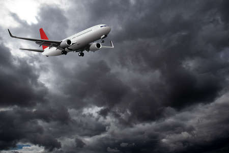 Commercial passenger plane with landing gear down flying through dramatic storm clouds