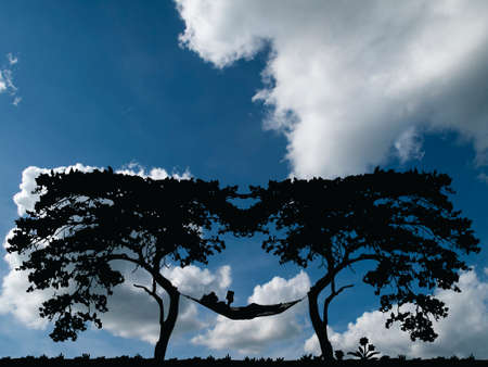 Silhouetted woman reading in a hammock resting between two trees with blue cloudy sky background