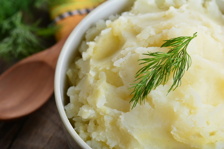 Mashed potatoes, boiled puree in ceramic pot on a wooden background