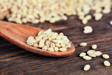 enamel: Pearl barley grain on a wooden table Stock Photo