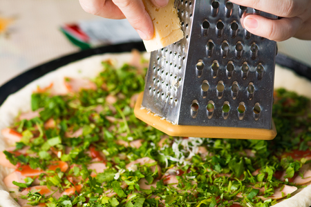 Cooking homemade pizza,  grate cheese Stock Photo