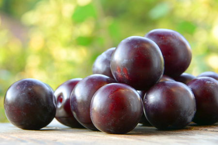 Plums on a wooden table in the garden Stock Photo