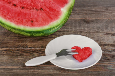 Piece of watermelon in heart shape on a plate Stock Photo