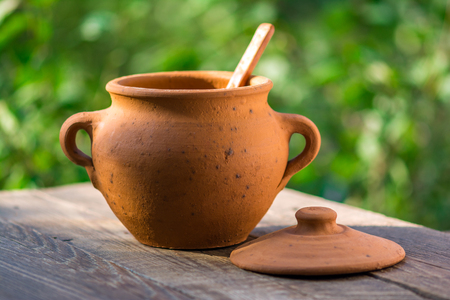 Empty clay pot on a wooden table in garden Stockfoto