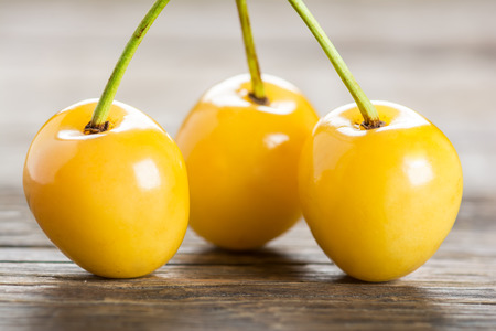 Yellow cherry on a wooden background