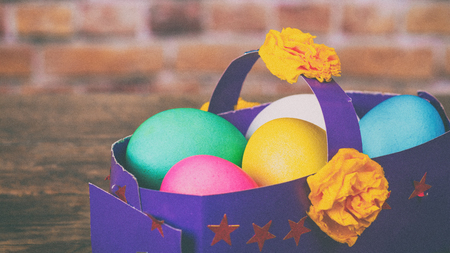 Colorful festive easter eggs in paper basket. Toned under the old film, added grain and noise