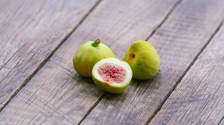 Ripe sweet figs on a wooden background
