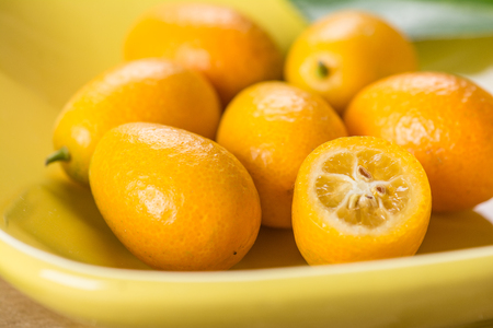 Kumquat on plate at wooden table Stock Photo