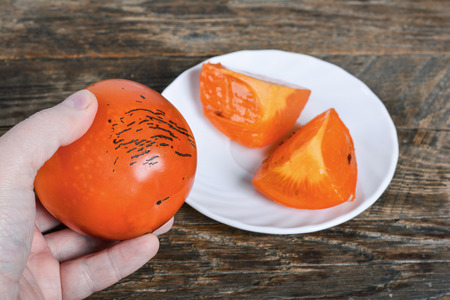 Juicy tropical persimmon fruit in hand Stock Photo