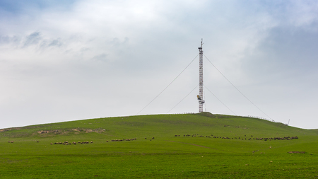 Cellular antenna tower on a green hill Stock Photo - 98872692
