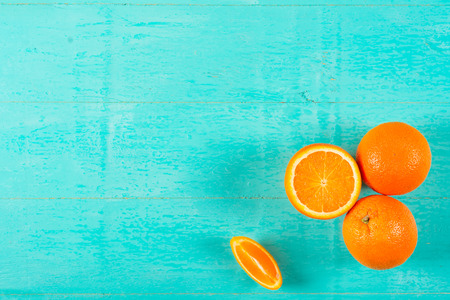 Ripe juicy oranges on a blue wooden background Stock Photo