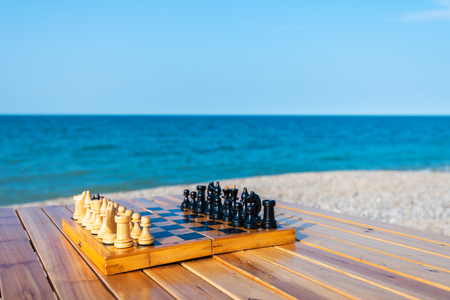 Chess board on the table by the sea Stock Photo