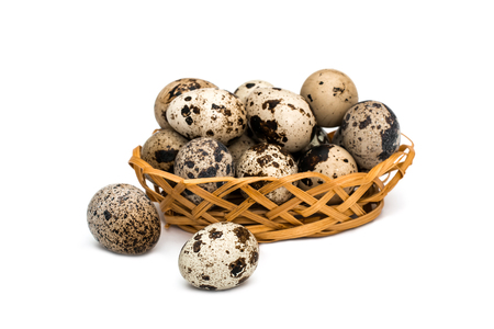 Quail eggs in wicker basket on white background