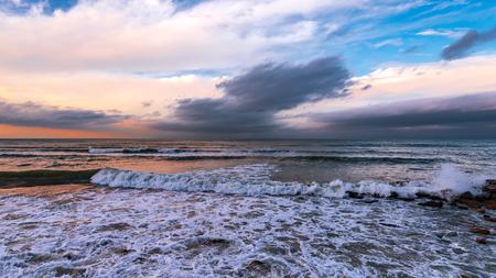 Seashore with cliffs, waves crashing on rocks