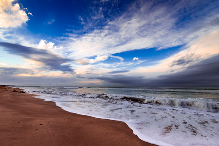Seashore, stormy sea and colorful clouds on the horizon