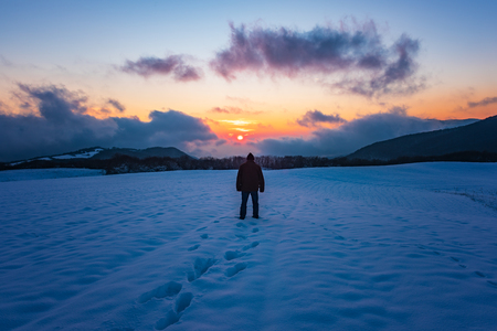 Man go on a snowy field Фото со стока