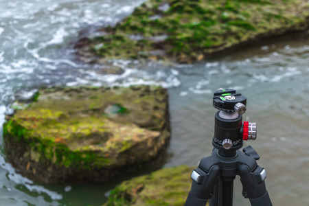 Professional tripod on a rock by the sea
