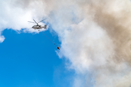 Rescue helicopter drops water extinguishes the fire Stock Photo