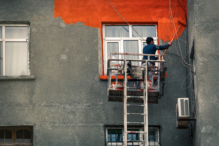 Worker paints the wall of a residential house
