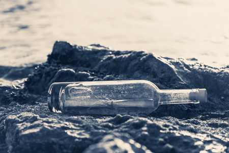 Message in a corked bottle on the shore, hope of salvation