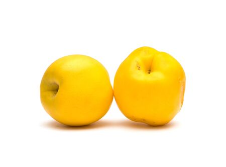 Juicy yellow nectarines on a white background