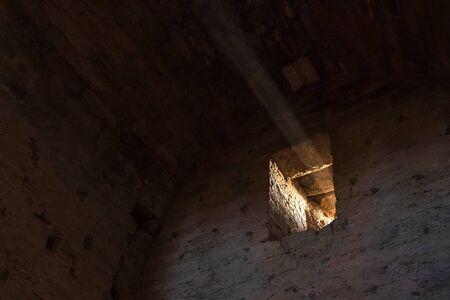 Raggio di luce nella finestra di un'antica fortezza in pietra