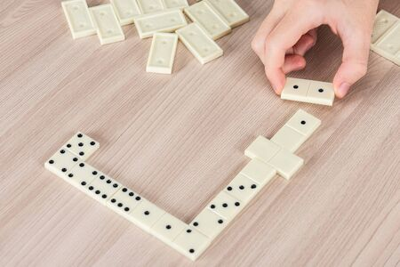 Person playing dominoes on a wooden table