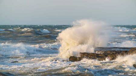 Big waves crash against coastal cliffs. Sea storm