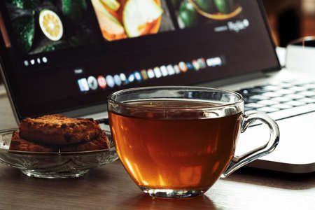 Glass cup with tea and cookies on a office desk with a laptop Tea break from loved job. Work online or offline or in office, freelancer job