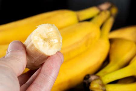 Ripe sliced banana in hand, eating