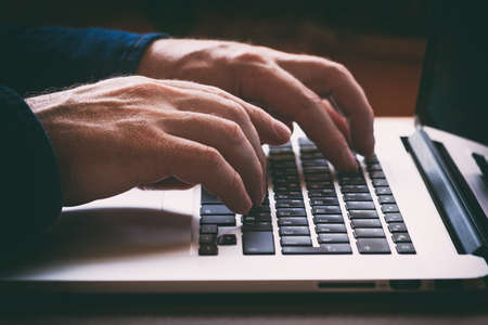 Hands on laptop keyboard typing text