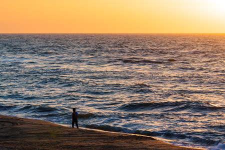 A lonely man walks along an empty beach