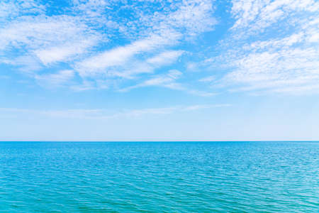 Calm clear blue sea and clouds on sky