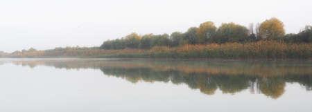 Beautiful reflections on a very still flat river at sunrise Zdjęcie Seryjne