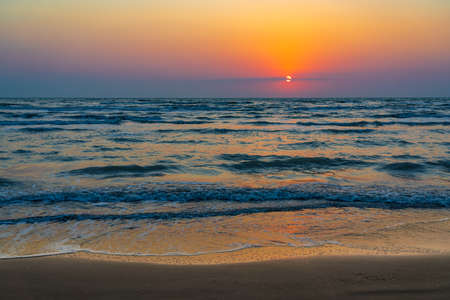 Colorful sunrise by the ocean shore