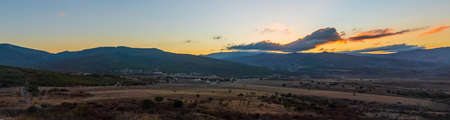 Colorful sunset over the mountains. Wide panorama overlooking the village and farm fields